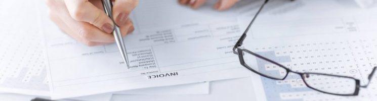 Diferenças entre NFE e NFCE - Pessoa assinando documentos e notas fiscais - Penta Certificação Digital