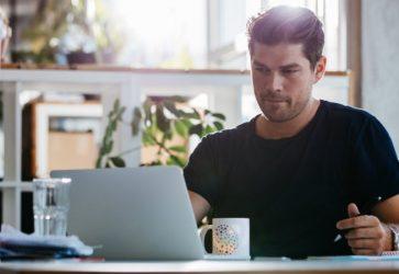 Homem sentando lendo artigo no computador