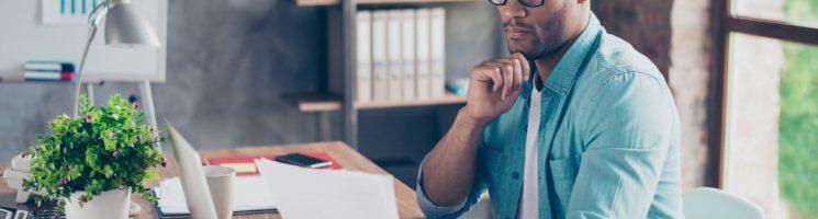 Homem negro olhando papel escritório de casa