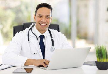 Médico sorrindo sentado digitando no computador | O que é o e-Médico e como ele pode ser utilizado?